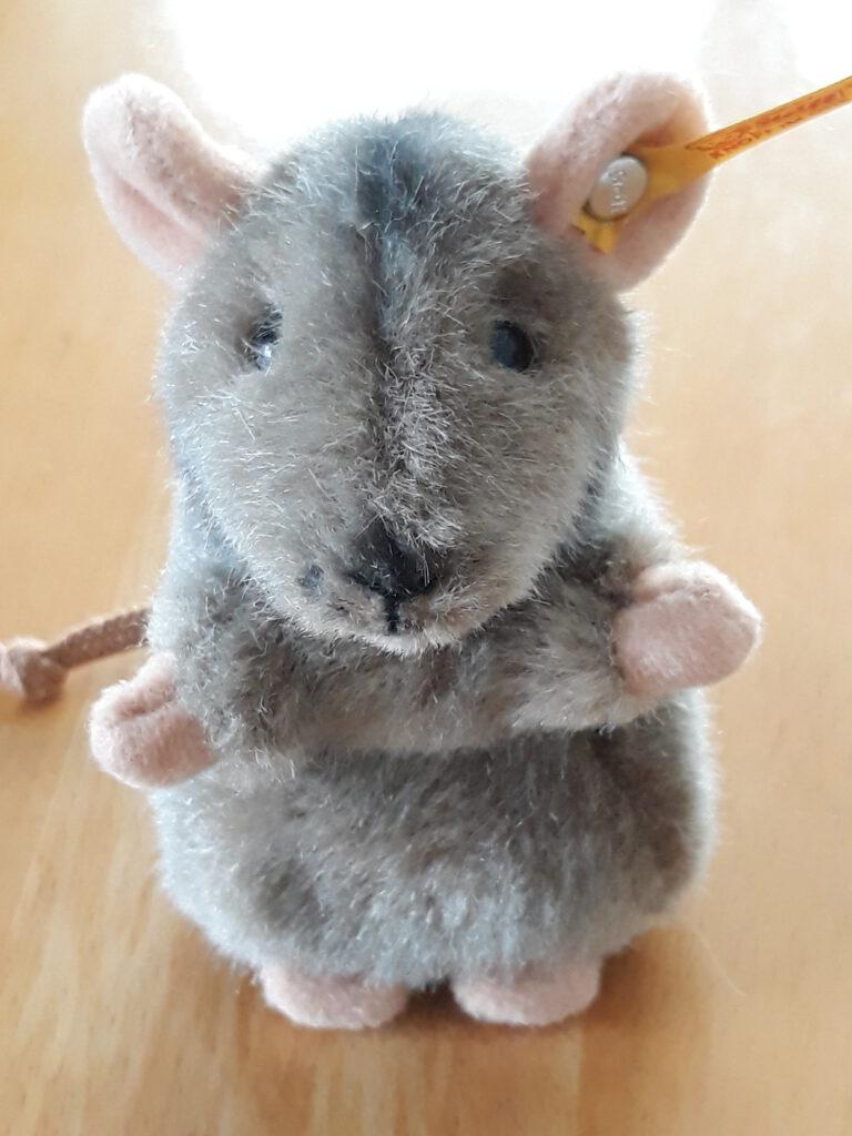 Die kleine Stoffmaus Friederike hat ein graues kuscheliges Fell und freut sich, wenn jemand sie streichelt.